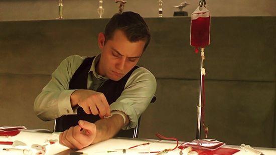 Jude Law prepara sangre y muestras de su cuerpo para ayudar a Ethan Hawke a pasar las pruebas genéticas. Columbia Pictures.